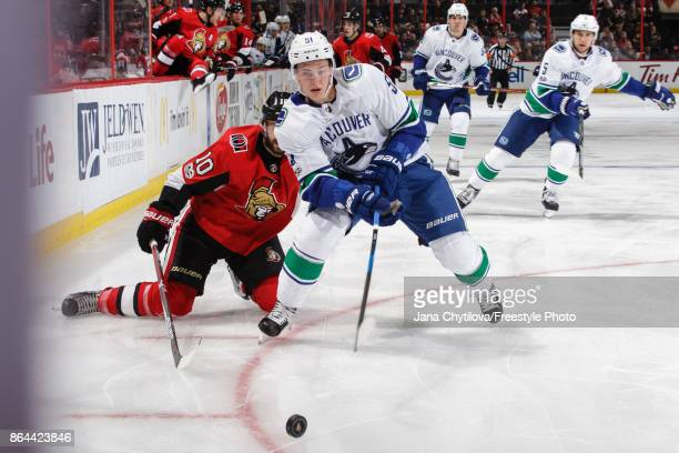 Troy Stecher of the Vancouver Canucks chips the puck past Tom Pyatt of the Ottawa Senators at Canadian Tire Centre on October 17 2017 in Ottawa...