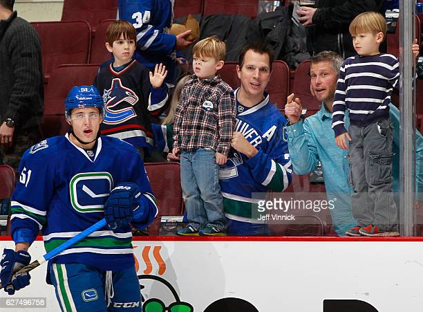 Troy Stecher of the Vancouver Canucks skates by some young Vanouver fans during their NHL game against the Toronto Maple Leafs at Rogers Arena...