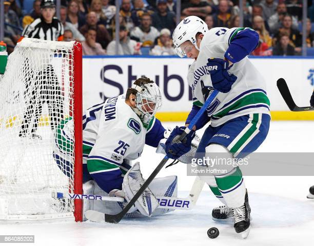 Troy Stecher of the Vancouver Canucks tries to clear the puck from in front of Jacob Markstrom during the second period against the Buffalo Sabres at...