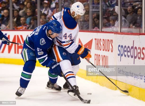 Troy Stecher of the Vancouver Canucks tries to knock Zack Kassian of the Edmonton Oilers off the puck in NHL action on April 8 2017 at Rogers Arena...