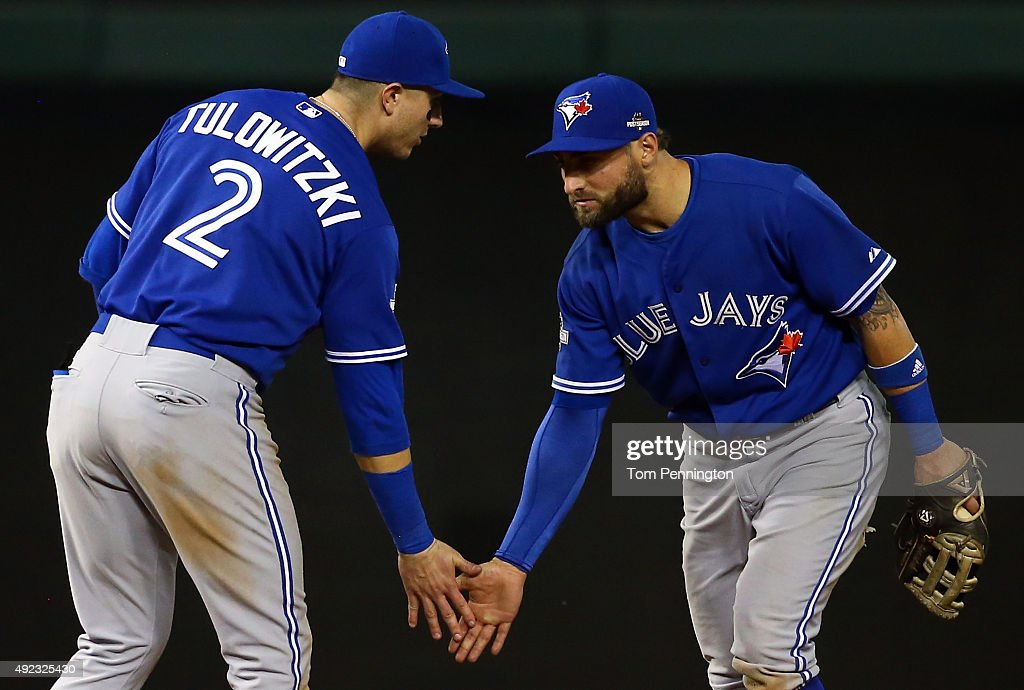 Troy Tulowitzki #2 and Kevin Pillar #11 of the Toronto Blue Jays celebrate after defeating the Texas Rangers in game three of the American League Division Series on October 11, 2015 in Arlington, Texas. The Blue Jays defeated the Rangers with a score of 5 to 1.