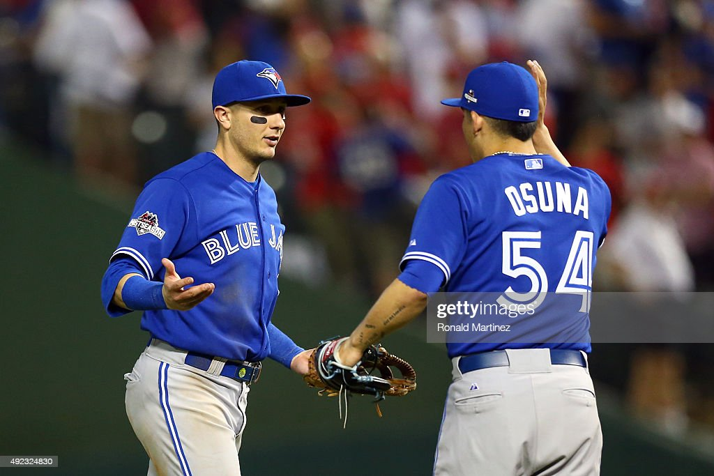 Troy Tulowitzki #2 and Roberto Osuna #54 of the Toronto Blue Jays celebrate after defeating the Texas Rangers in game three of the American League Division Series on October 11, 2015 in Arlington, Texas. The Blue Jays defeated the Rangers with a score of 5 to 1.