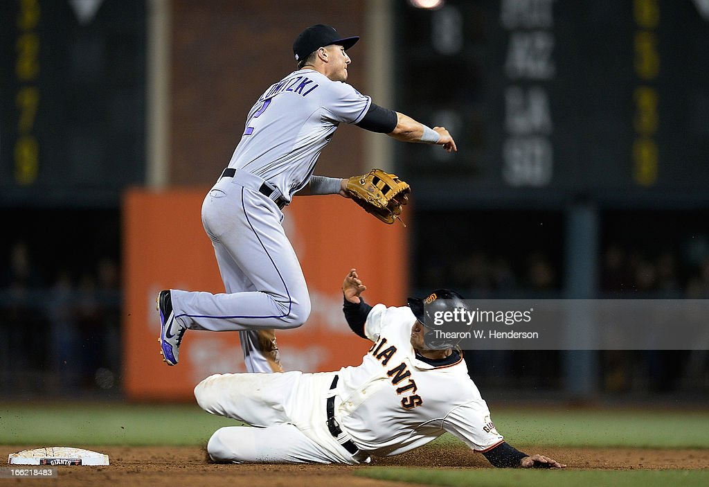 Troy Tulowitzki #2 of the Colorado Rockies gets his throw off to first base completing the double-play, while avoiding the slide of Hunter Pence #8 of the San Francisco Giants in the six inning at AT&T Park on April 9, 2013 in San Francisco, California.