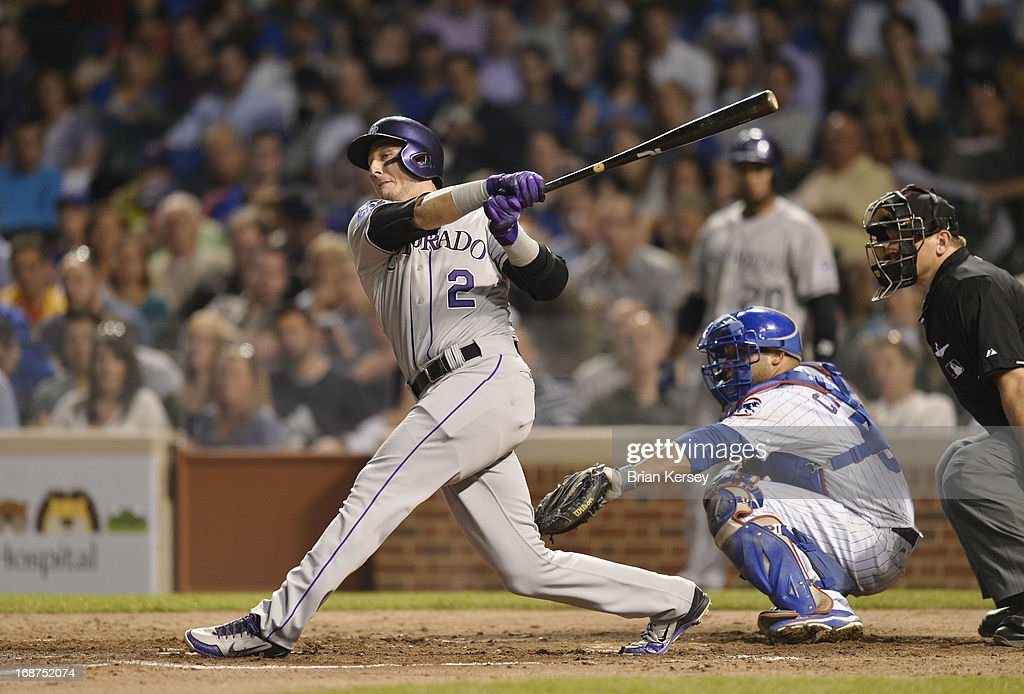 <a gi-track='captionPersonalityLinkClicked' href=/galleries/search?phrase=Troy+Tulowitzki&family=editorial&specificpeople=757353 ng-click='$event.stopPropagation()'>Troy Tulowitzki</a> #2 of the Colorado Rockies hits an RBI double, scoring Carlos Gonzalez (not pictured) as <a gi-track='captionPersonalityLinkClicked' href=/galleries/search?phrase=Welington+Castillo&family=editorial&specificpeople=4959193 ng-click='$event.stopPropagation()'>Welington Castillo</a> #53 of the Chicago Cubs catches during the fifth inning on May 14, 2013 at Wrigley Field in Chicago, Illinois.