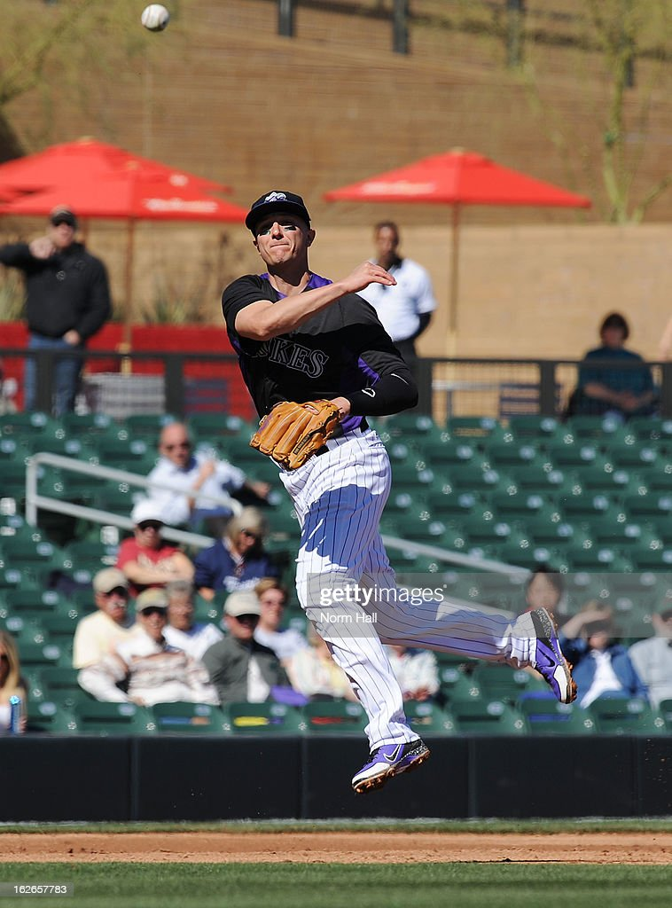 Troy Tulowitzki #2 of the Colorado Rockies makes a leaping throw against the Texas Rangers at Salt River Field on February 25, 2013 in Scottsdale, Arizona.