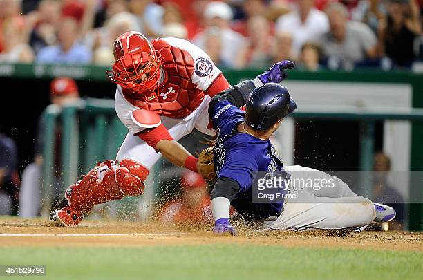 Troy Tulowitzki of the Colorado Rockies scores in the sixth inning ahead of the tag of Wilson Ramos of the Washington Nationals at Nationals Park on...