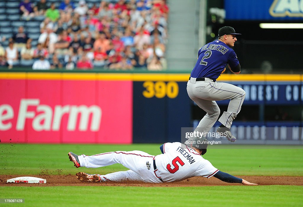 <a gi-track='captionPersonalityLinkClicked' href=/galleries/search?phrase=Troy+Tulowitzki&family=editorial&specificpeople=757353 ng-click='$event.stopPropagation()'>Troy Tulowitzki</a> #2 of the Colorado Rockies turns a double play against <a gi-track='captionPersonalityLinkClicked' href=/galleries/search?phrase=Freddie+Freeman&family=editorial&specificpeople=5743987 ng-click='$event.stopPropagation()'>Freddie Freeman</a> #5 of the Atlanta Braves at Turner Field on July 31, 2013 in Atlanta, Georgia.