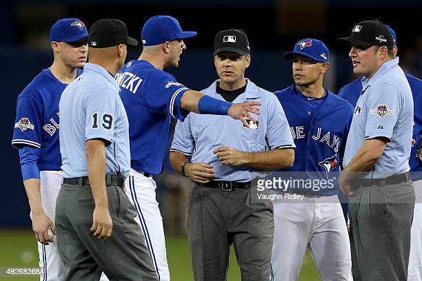 Troy Tulowitzki of the Toronto Blue Jays argues a call in seventh inning with the umpires as the Texas Rangers score a run after the throw by Russell...