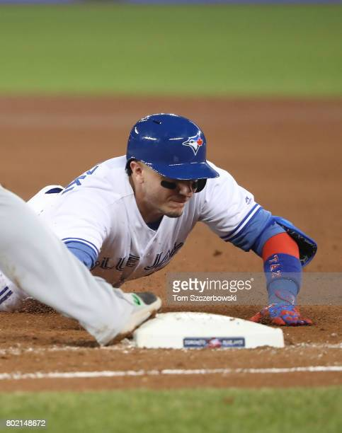Troy Tulowitzki of the Toronto Blue Jays dives back to first base but cannot get back in time as he is doubled off on a line drive in the seventh...