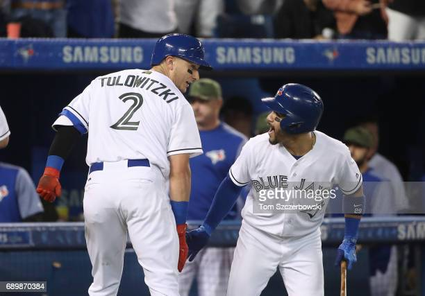 Troy Tulowitzki of the Toronto Blue Jays is congratulated by Devon Travis after hitting a grand slam home run in the third inning during MLB game...