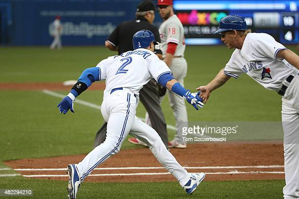 Troy Tulowitzki of the Toronto Blue Jays is congratulated by first base coach Tim Leiper after hitting a tworun home run in the second inning during...