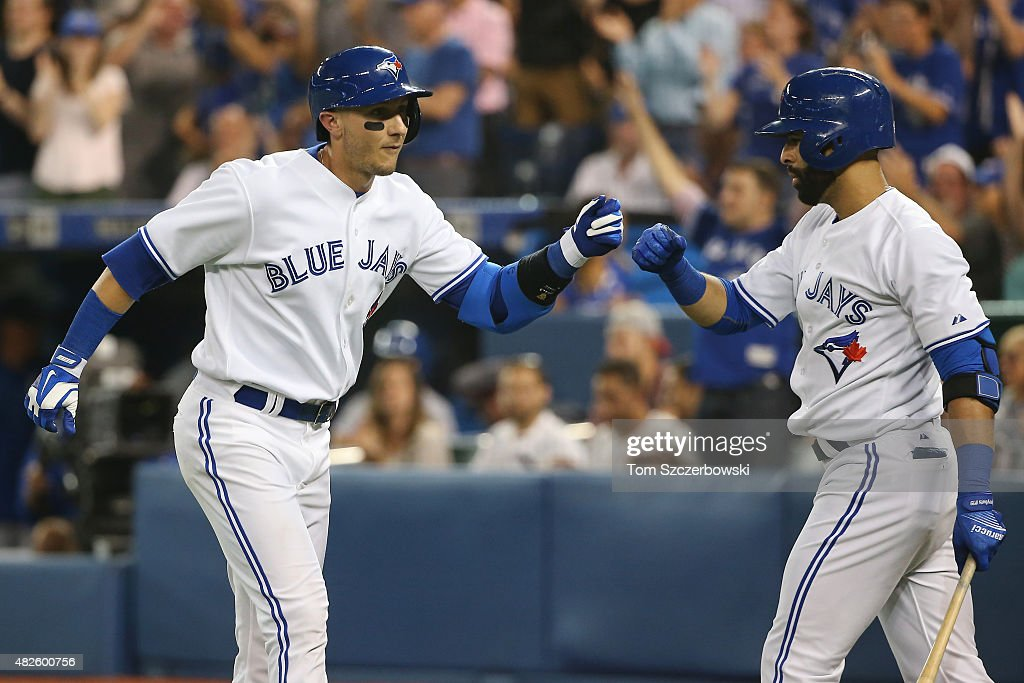Troy Tulowitzki #2 of the Toronto Blue Jays is congratulated by Jose Bautista #19 after scoring a run in the seventh inning during MLB game action against the Kansas City Royals on July 31, 2015 at Rogers Centre in Toronto, Ontario, Canada.