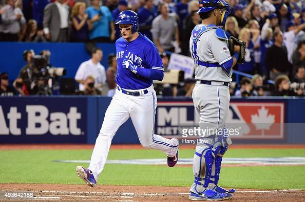 Troy Tulowitzki of the Toronto Blue Jays scores a run in front of Salvador Perez of the Kansas City Royals to take a 71 lead in the eighth inning...