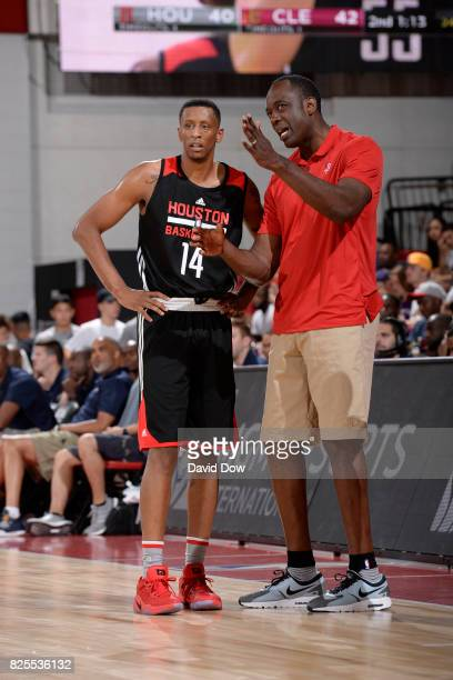Troy Williams of the Houston Rockets and Roy Rogers speak on the sideline against the Cleveland Cavaliers during the 2017 Las Vegas Summer League on...