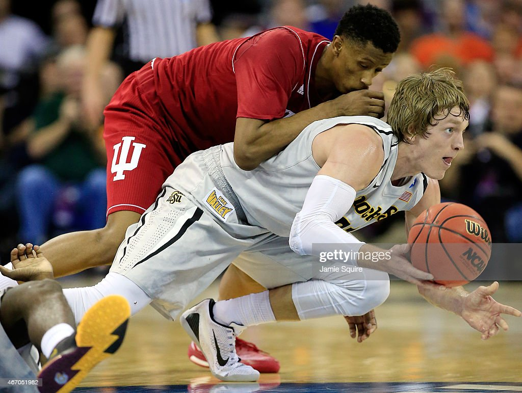 Troy Williams #5 of the Indiana Hoosiers and Ron Baker #31 of the Wichita State Shockers dive for a loose ball during the second round of the 2015 NCAA Men's Basketball Tournament at the CenturyLink Center on March 20, 2015 in Omaha, Nebraska.