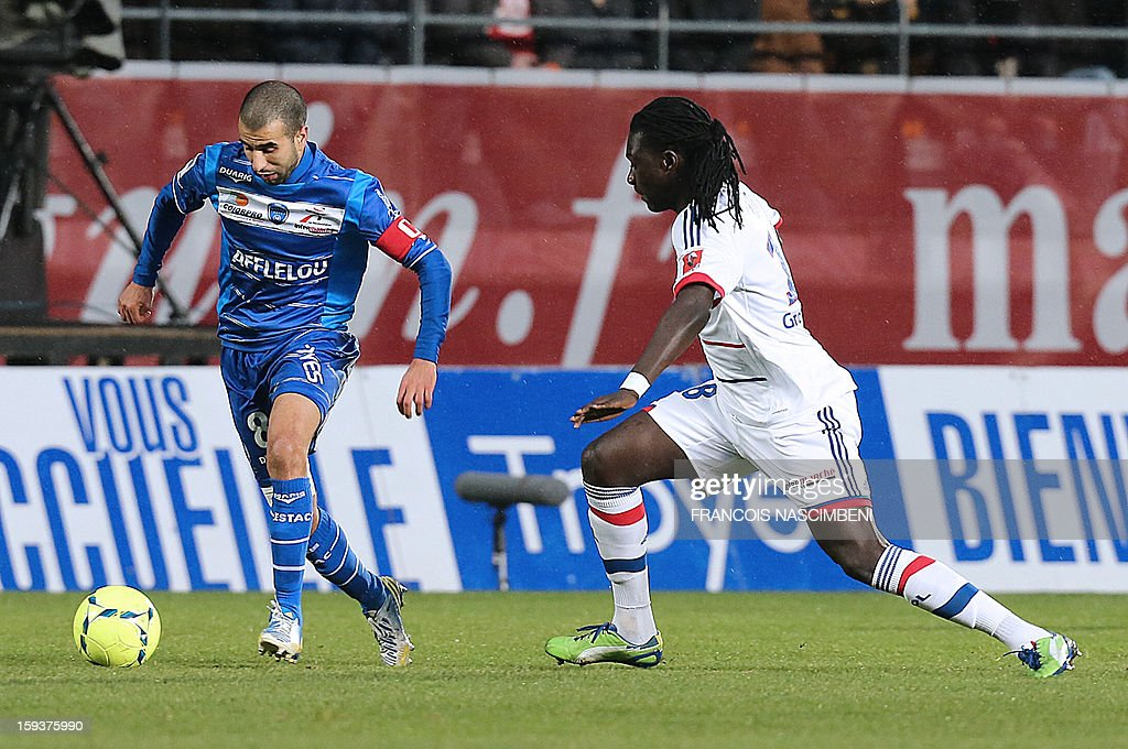 Troyes' defender Mounir Obbadi (L) vies with Lyon's forward Bafetimbi Gomis (R) during a French L1 football match between Troyes and Lyon on January 12, 2013 at the Aube Stadium in Troyes.