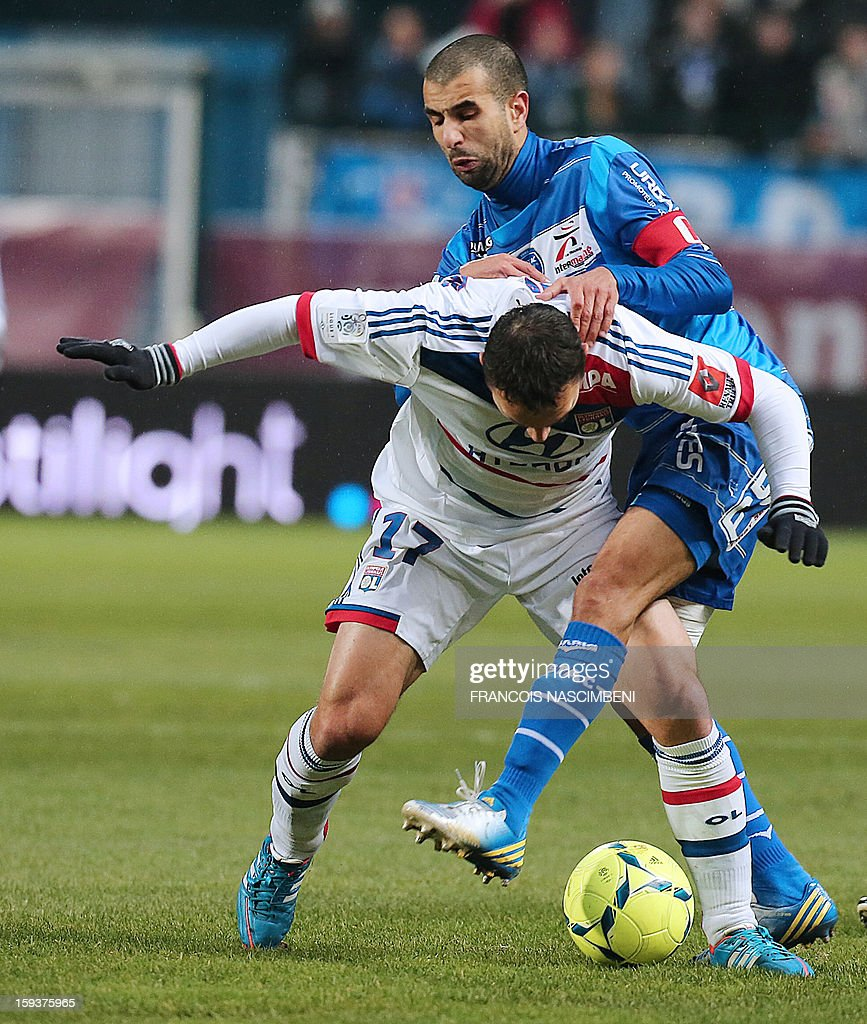Troyes' defender Mounir Obbadi (R) vies with Lyon's midfielder Steed Malbranque (L) during a French L1 football match between Troyes and Lyon on January 12, 2013 at the Aube Stadium in Troyes.