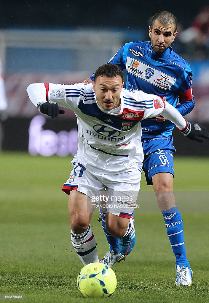 Troyes' defender Mounir Obbadi (R) vies with Lyon's midfielder Steed Malbranque (L) during the French L1 football match Troyes vs Lyon on January 12, 2013 at the Aube Stadium in Troyes, northern France. PHOTO