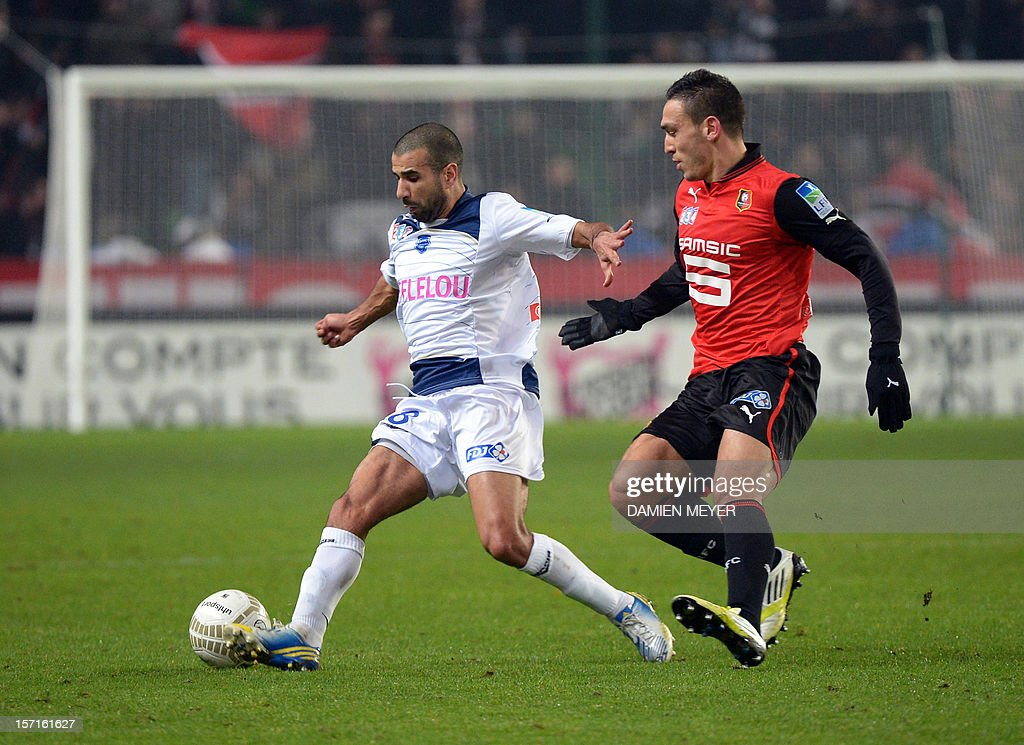 Troyes' French defender Eloge Enza-Yamissi (L) fights for the ball with Rennes' French forward Mevlut Erding during the French cup football match Rennes against Troyes on November 29 , 2012 at the route de Lorient stadium in Rennes, western France.