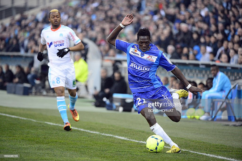 Troyes' French defender Fabrice Nsakala (R) controls the ball near Marseille's Ghanaian forward Jordan Ayew during the French L1 football match Olympique of Marseille vs Troyes at the Velodrome Stadium in Marseille on March 3, 2013.