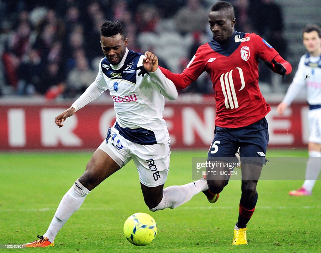 Troyes' French forward Jean Christophe Rahebeck (L) vies with Lille's French defender Dijbril Sidibe during the French L1 football match Lille vs Troyes on February 2, 2013 at the Grand Stade Stadium in Villeneuve d'Ascq.