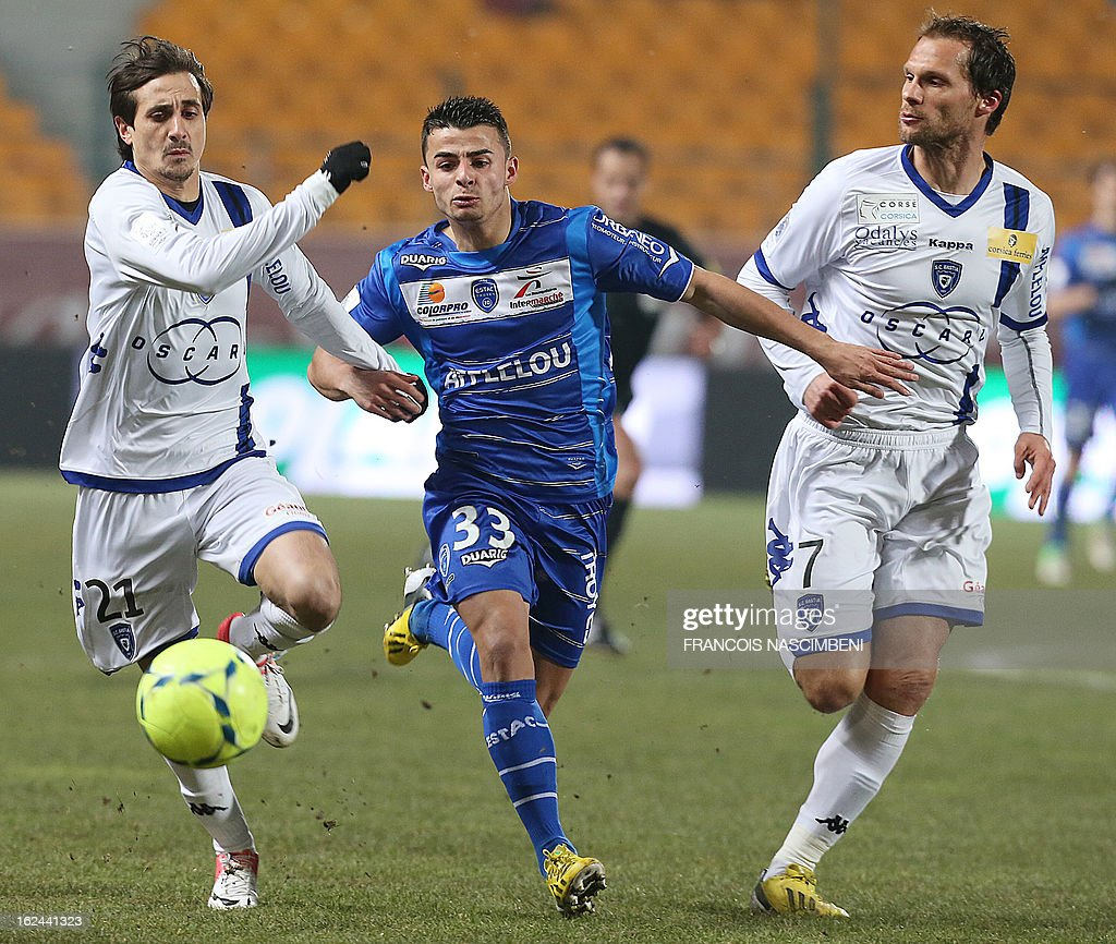 Troyes' French forward Jean Corentin (Center) vies with Bastia's Algerian defender Fethi Harek (L) and Bastia's French defender Sylvain Marchal (R), on February 23, 2013 during the French L1 football match Troyes vs Bastia in the Aube Stadium in Troyes.
