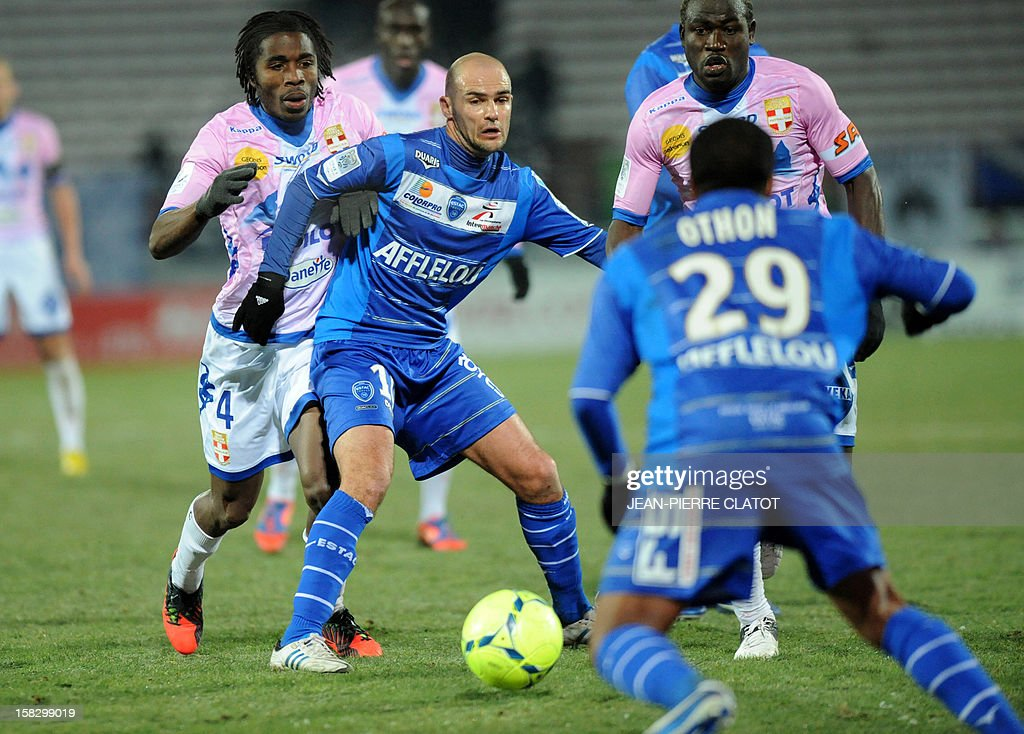 Troyes' French midfielder Benjamin Nivet (C) tries to escape from Evian's defenders during their French L1 football match Evian (ETGFC) vs Troyes (ESTAC) on December 12, 2012 at the city stadium Parc des sports in Annecy, eastern France.