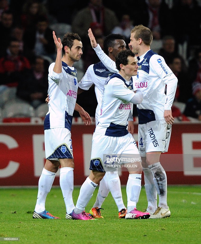 Troyes' French midfielder Fabien Camus (L) is congratuled by team mates after scoring a goal during a French L1 football match between Lille and Troyes on February 2, 2013 at Grand Stade in Villeneuve d'Ascq. AFP PHOTO / PHILIPPE HUGUEN