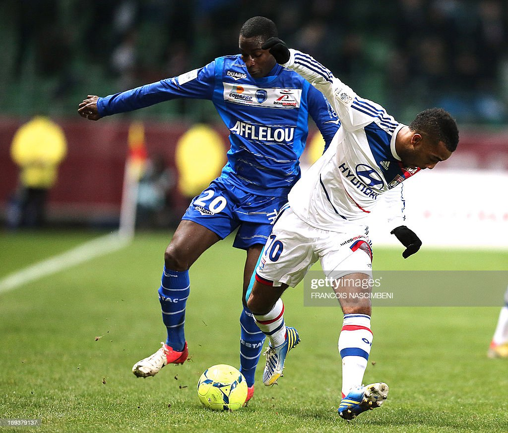 Troyes' French midfielder granddi Ngoyi (L) vies with Lyon's midfilder Alexandre Lacazette during a French L1 football match between Troyes and Lyon on January 12, 2013 at the Aube Stadium in Troyes.