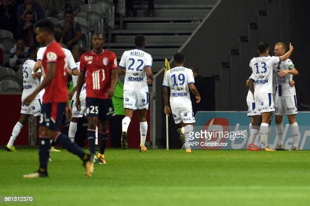 Troyes' French midfielder Stephane Darbion celebrates with teammates after scoring a goal during the French L1 football match between Lille and...
