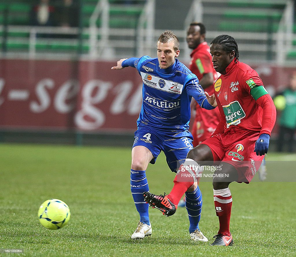 Troyes' French midfielder Stephane Darbion (L) vies with Brest's French defender Bernard Mendy (R) during the French L1 football match Troyes vs Brest on January 26, 2013 at the Aube stadium in Troyes. PHOTO FRANCOIS NASCIMBENI