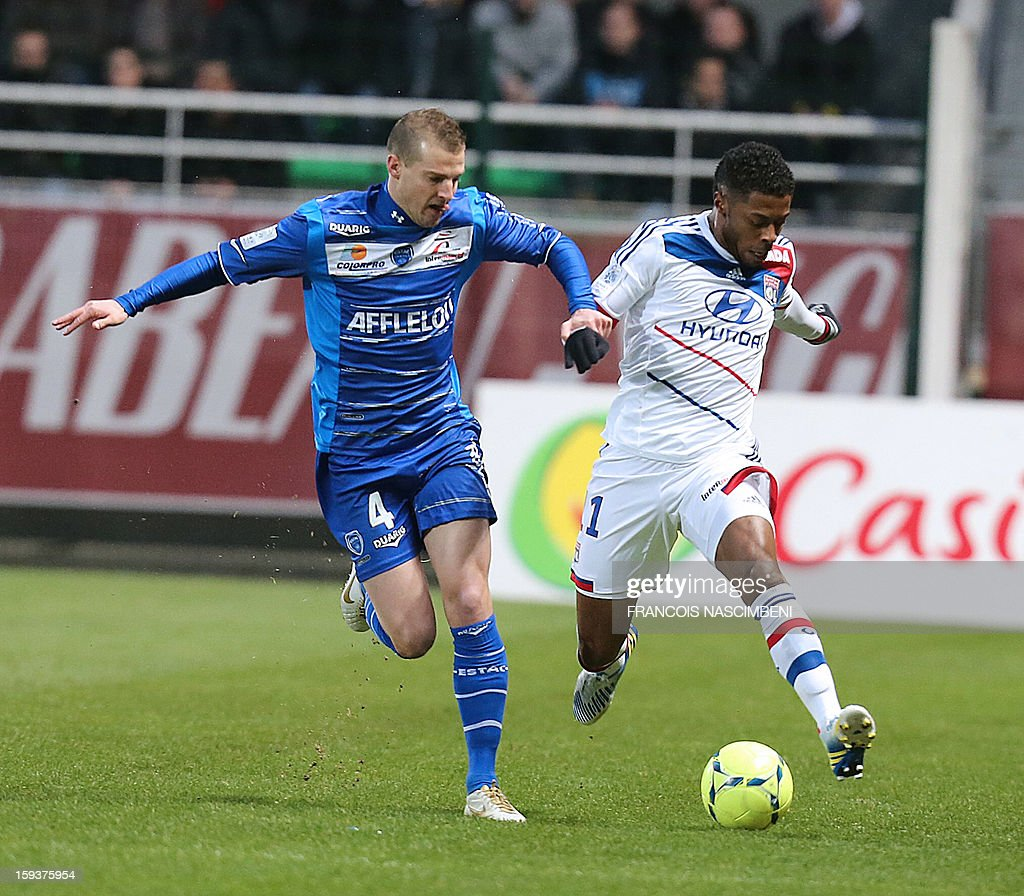 Troyes' French midfielder Stephane Darbion (L) vies with Lyon's forward Bastos (R) during a French L1 football match between Troyes and Lyon on January 12, 2013 at the Aube Stadium in Troyes.