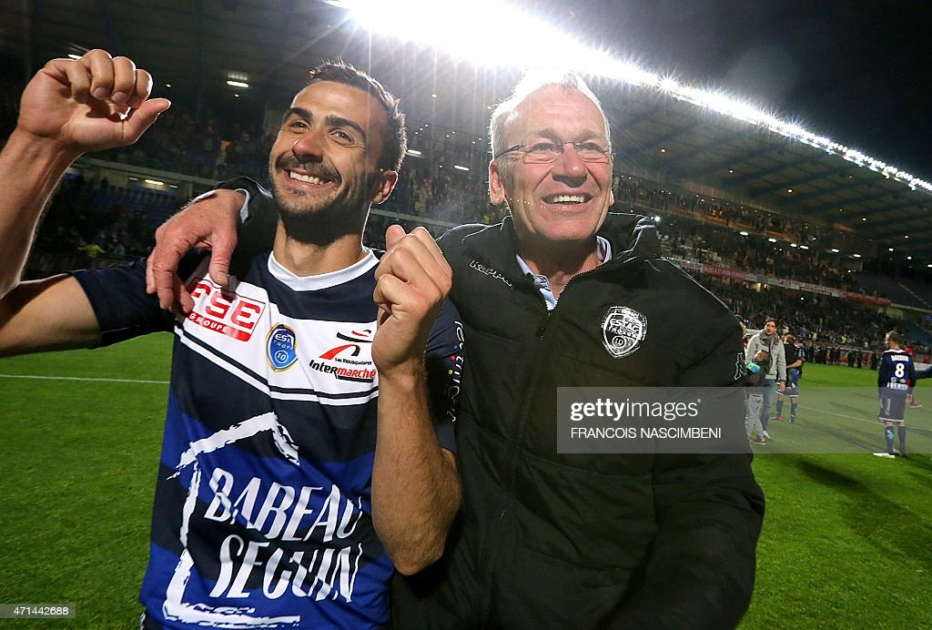 Troyes' head coach Jean-Marc Furlan (R) and Troyes' defender Matthieu Saunier celebrate after Troyes won the French L2 football match against Angers at the Aube Stadium in Troyes on April 28, 2015.