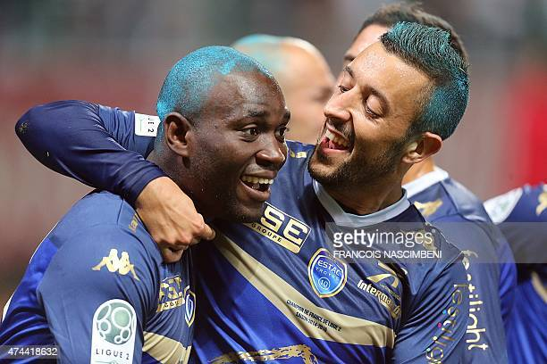 Troyes' midfielder forward Henri Bienvenu celebrates with teammate after scoring a goal during the French Football match between Troyes and...