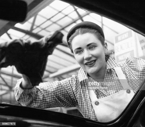 Très belle jeune femme travaillant dans un garage nettoie un parebrise