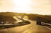 Truck driving on highway winding through hilly landscape at sunset