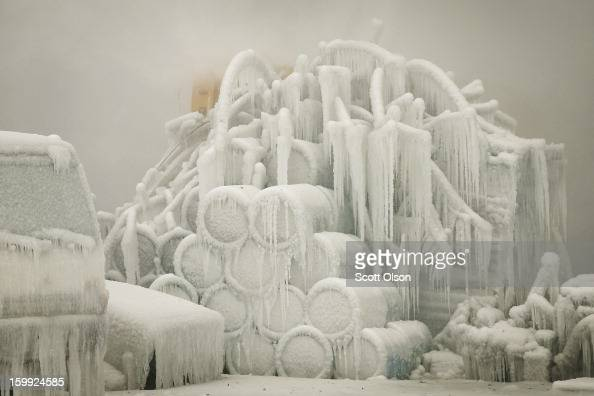A truck and chemical drums are covered with ice as firefighters help to extinguish a massive blaze at a vacant warehouse on January 23 2013 in...