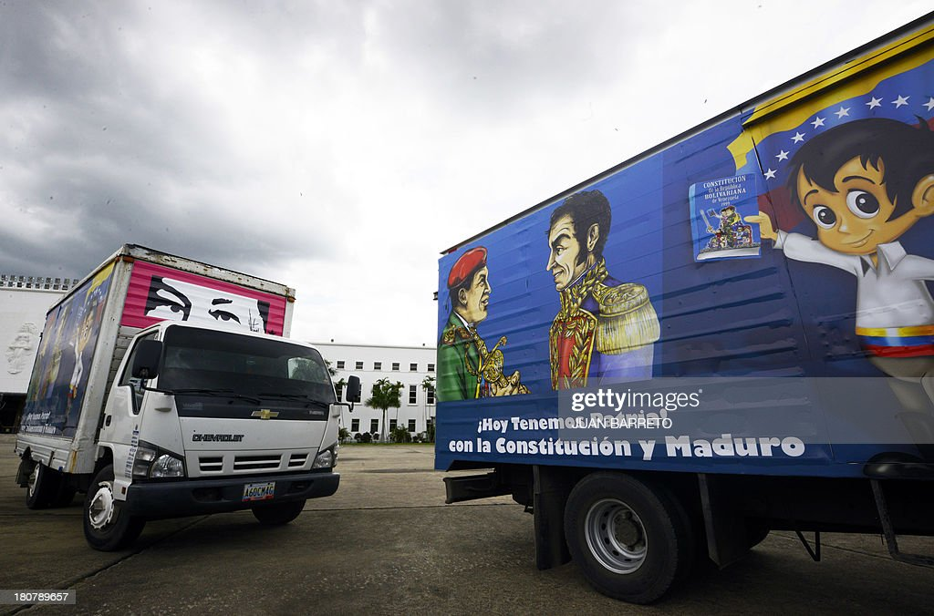 Truck arrive at a school in Caracas, to deliver Venezuelan Constitutions with drawings depicting late President Hugo Chavez (L at centre) and Latin American independence hero Simon Bolivar, at a school in Caracas, on September 16, 2013. AFP PHOTO