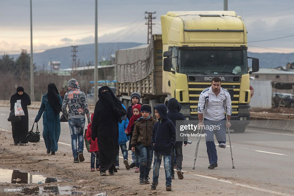 A truck arriving at the border passes people walking towards a temporary housing complex located at the closed Turkish border gate on February 7, 2016 in Kilis, Turkey. According to Turkish officials some 35,000 Syrian refugees have massed on the Syrian/Turkish border after fleeing Russian airstrikes and a regime offensive surrounding the city of Aleppo in northern Syria.