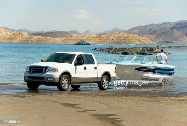 A truck backing a boat off of a trailer and into the water