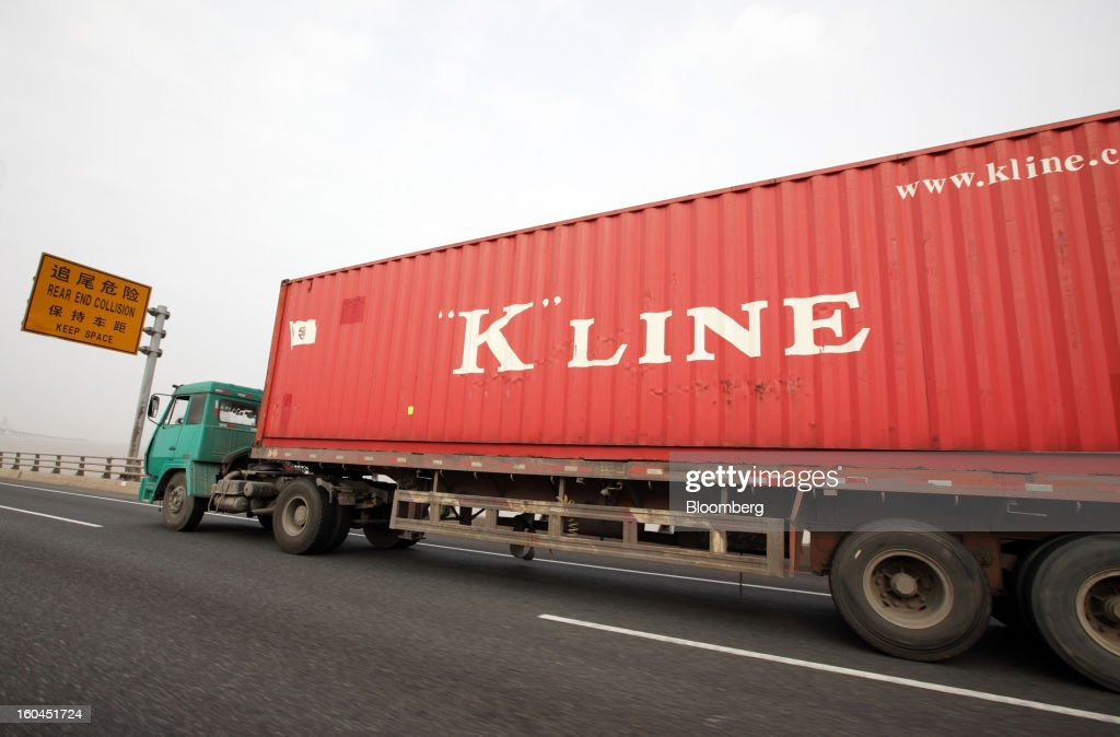 A truck carries a Kawasaki Kisen Kaisha Ltd. shipping container near the Yangshan Deep Water Port in Shanghai, China, on Thursday, Jan. 31, 2013. China's economic growth accelerated for the first time in two years as government efforts to revive demand drove a rebound in industrial output, retail sales and the housing market. Photographer: Tomohiro Ohsumi/Bloomberg via Getty Images