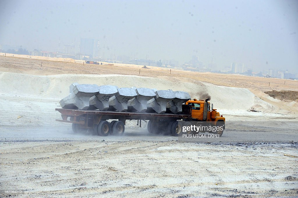 A truck carries accropode, a sea defence barrier designed and built to withstand the most severe tidal surges, on January 31, 2013 in Lagos, during the building of the three and a half kilometre long sea defence barrier called 'The Great Wall of Lagos' built to shield from coastal erosion Eko Atlantic, a new city born from the Altantic ocean in Lagos. Nigeria's President Goodluck Jonathan and former US President Bill Clinton dedicated on February 21, 2013 the new 5-million-square-metre Eko Atlantic City, which is to be the first modern smart city in Africa to be built on reclaimed land from the Atlantic Ocean. AFP PHOTO/PIUS UTOMI EKPEI