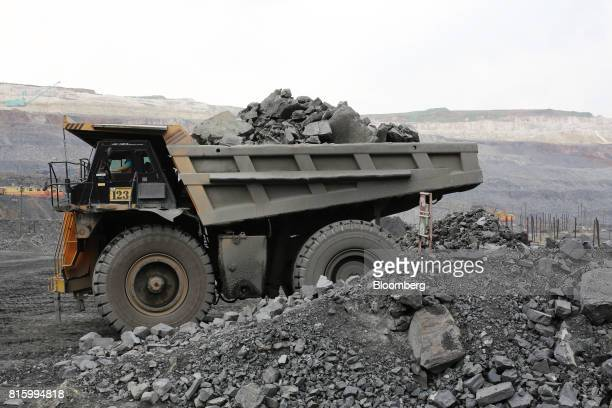 A truck carries excavated iron ore from the open pit of the Lebedinsky GOK iron ore mining and processing plant operated by MetalloinvestHolding Co...