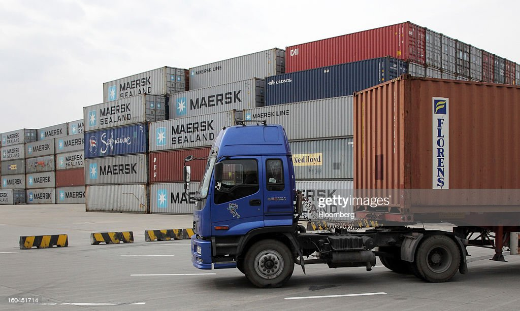 A truck carrying a shipping container drives past containers stacked at the Yangshan Deep Water Port in Shanghai, China, on Thursday, Jan. 31, 2013. China's economic growth accelerated for the first time in two years as government efforts to revive demand drove a rebound in industrial output, retail sales and the housing market. Photographer: Tomohiro Ohsumi/Bloomberg via Getty Images