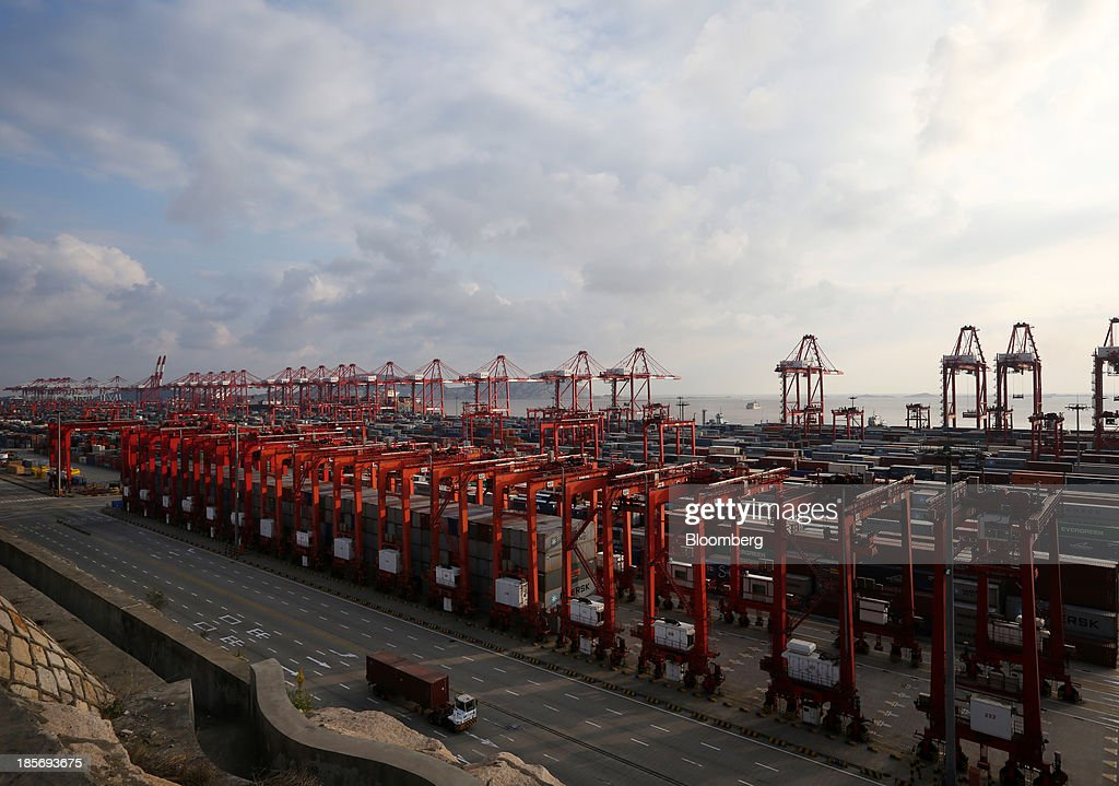 A truck carrying a shipping container drives past cranes at the Yangshan Deep Water Port, part of China (Shanghai) Pilot Free Trade Zone's Yangshan free trade port area, in Shanghai, China, on Wednesday, Oct. 23, 2013. The area is a testing ground for free-market policies that Premier Li Keqiang has signaled he may later implement more broadly in the world's second-largest economy. Photographer: Tomohiro Ohsumi/Bloomberg via Getty Images