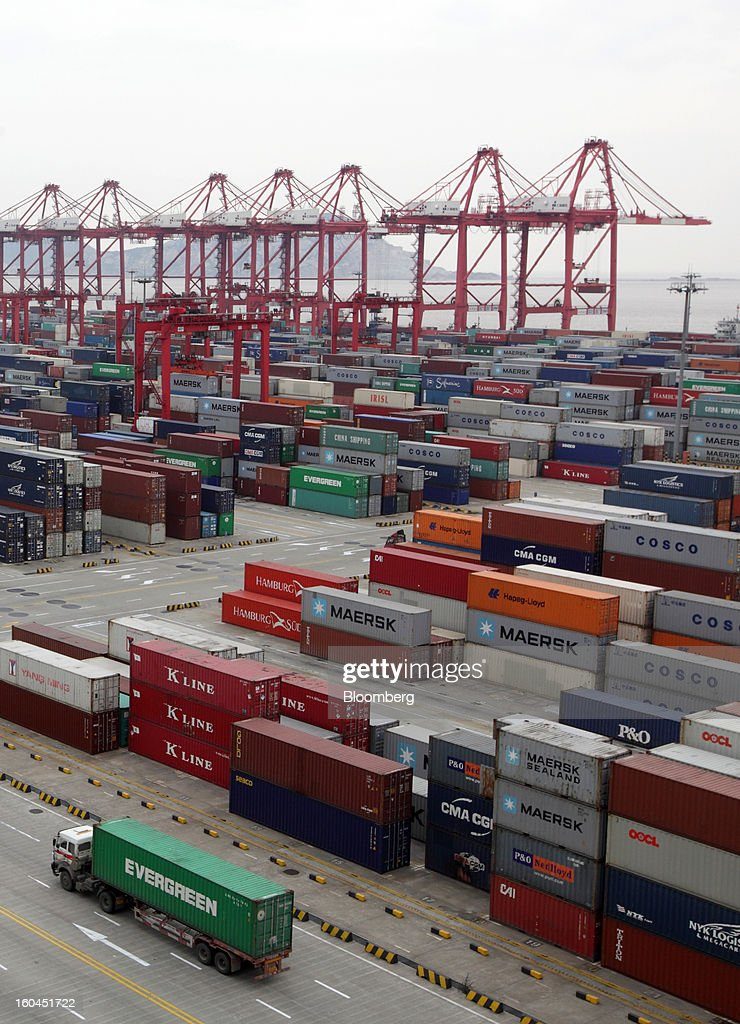 A truck carrying an Evergreen Marine Corp. container drives past containers stacked at the Yangshan Deep Water Port in Shanghai, China, on Thursday, Jan. 31, 2013. China's economic growth accelerated for the first time in two years as government efforts to revive demand drove a rebound in industrial output, retail sales and the housing market. Photographer: Tomohiro Ohsumi/Bloomberg via Getty Images