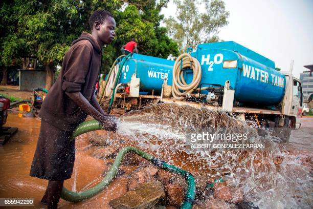 A truck driver collects water directly pumped from the Nile river on March 21 2017 in Juba South Sudan to distribute to local residents for drinking...