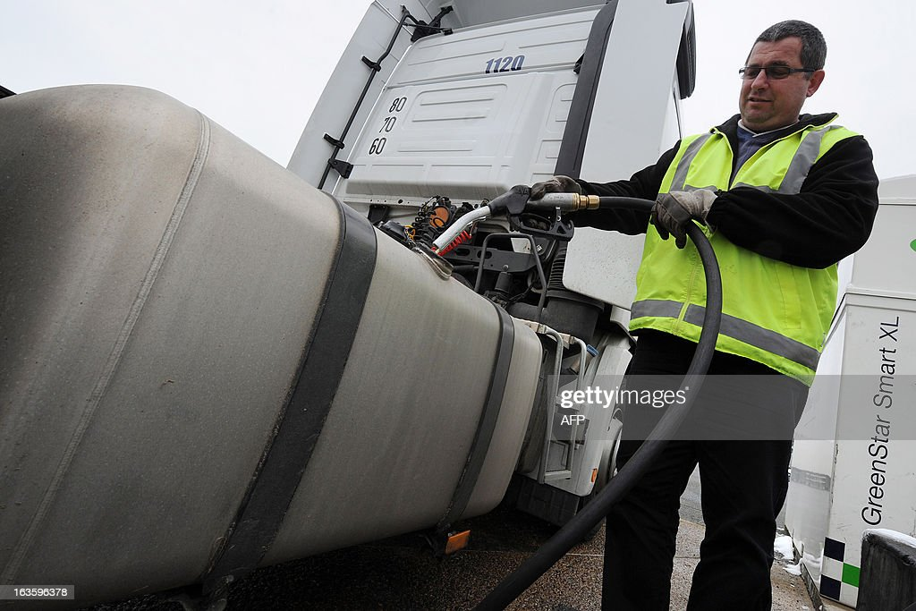 A truck driver fills a truck's tank with diesel in the yard of Transport Robineau company in Soulitre, western France, on March 12, 2013.