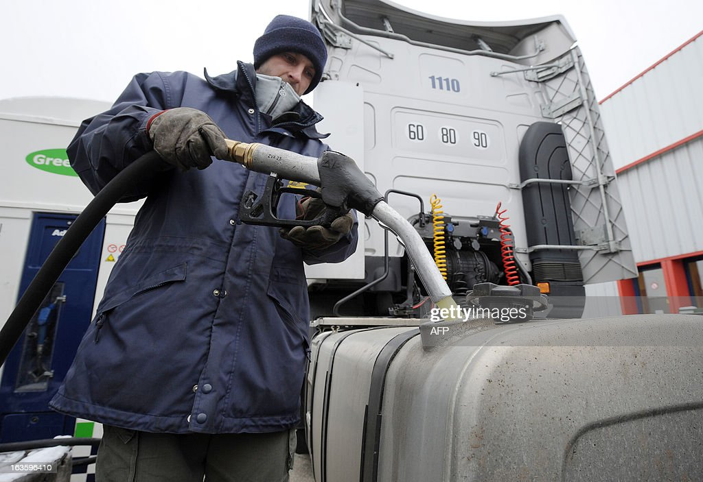 A truck driver fills the tank of his truck with diesel in the yard of Transport Robineau company in Soulitre, western France, on March 12, 2013. AFP PHOTO / JEAN-FRANCOIS MONIER