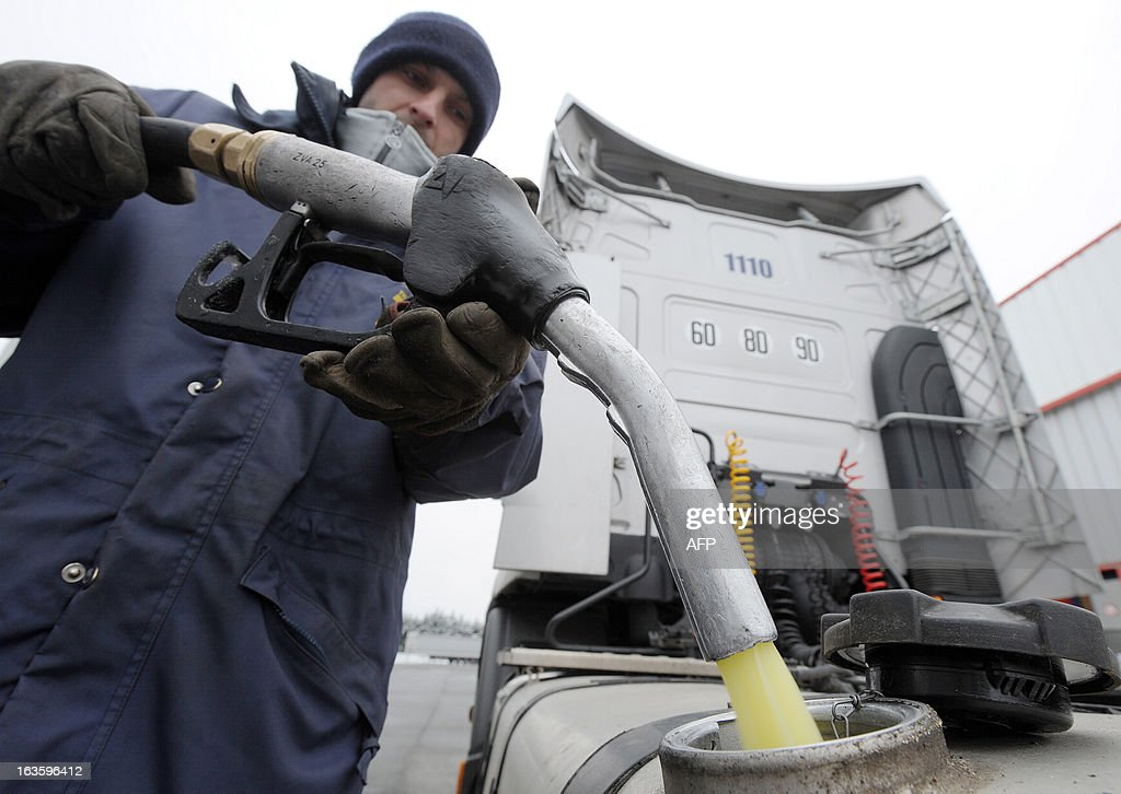 A truck driver fills the tank of his truck with diesel in the yard of Transport Robineau company in Soulitre, western France, on March 12, 2013.